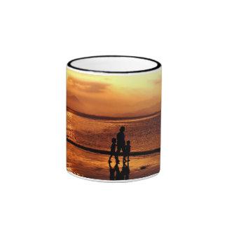 El caminar en la playa en la puesta del sol taza