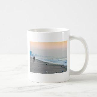 El caminar en la playa en la puesta del sol tazas de café