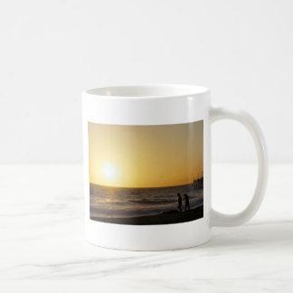El caminar en la puesta del sol taza de café