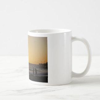 El caminar en la puesta del sol tazas de café