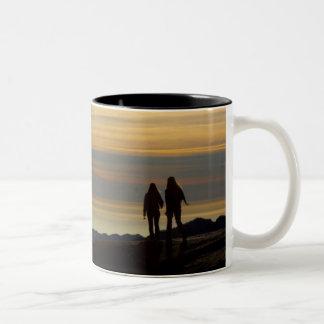 El caminar en puesta del sol taza de café