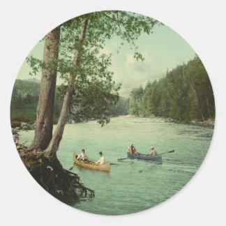 El Canoeing en una corriente de la montaña de Pegatina Redonda