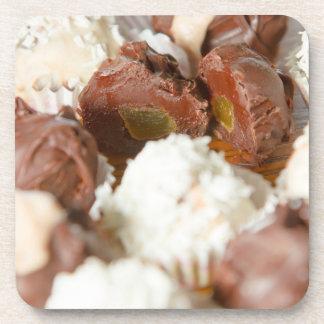 El caramelo/los dulces blancos y oscuros tapa los  posavasos de bebida
