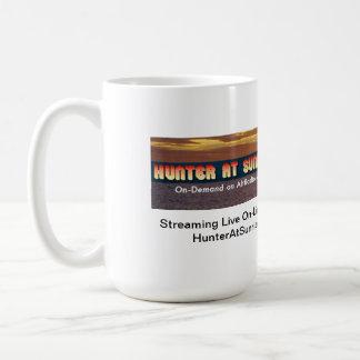 El cazador en la salida del sol enfría hacia fuera taza de café