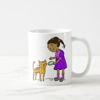 El chica alimenta el gato tazas