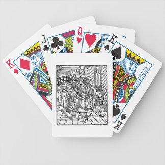 El cirujano dirige mientras que un ayudante se rom barajas de cartas
