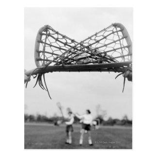 El comienzo del juego en un lacrosse combina con postal
