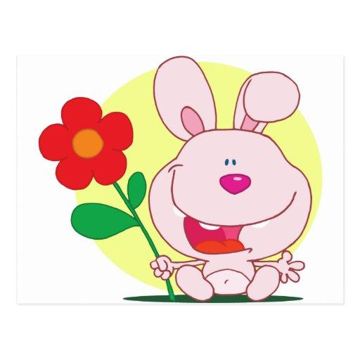El conejito feliz sostiene la flor postal