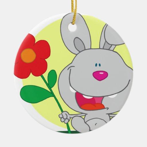 El conejito sospechado rosado feliz sostiene la adorno navideño redondo de cerámica