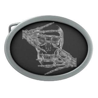 El cráneo esquelético con entrega la hebilla del hebillas de cinturon ovales