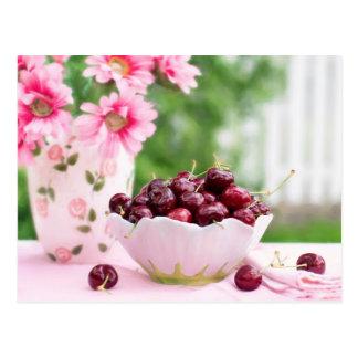 El cuenco de cerezas y de rosa florece la postal