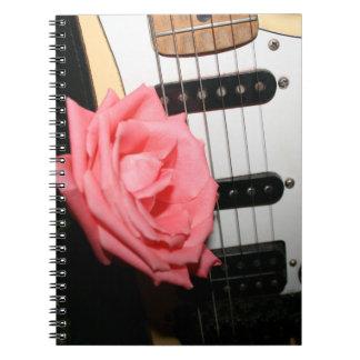El cuerpo color de rosa rosado de la guitarra ata note book