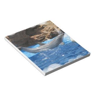 El delfín engaña la libreta bloc de papel