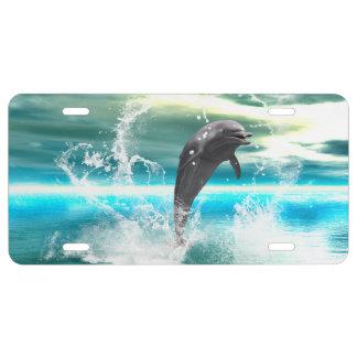 El delfín que salta en el mar con las ondas como placa de matrícula