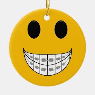El dentista apoya el ornamento adorno navideño redondo de cerámica