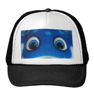 El dibujo animado feliz azul observa en el juguete gorra