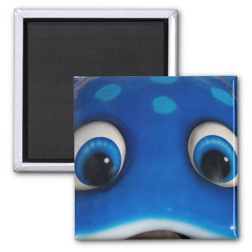 El dibujo animado feliz azul observa en el juguete iman de frigorífico