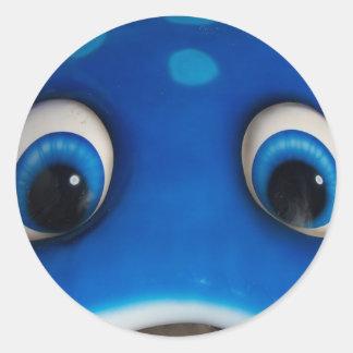 El dibujo animado feliz azul observa en el juguete etiqueta