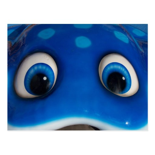 El dibujo animado feliz azul observa en el juguete tarjetas postales