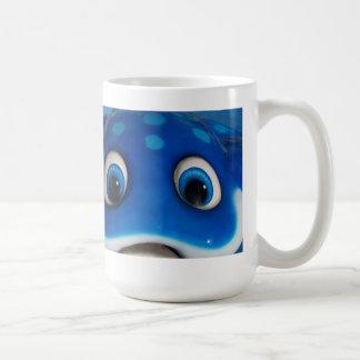 El dibujo animado feliz azul observa en el juguete taza