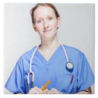 El doctor de sexo femenino adentro friega azulejo cuadrado grande
