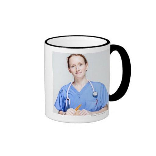 El doctor de sexo femenino adentro friega taza a dos colores