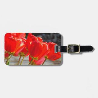 El equipaje marca las flores rojas de encargo del  etiqueta de maleta