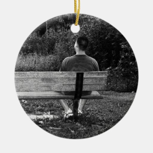 Él es solo en un banco de parque adorno redondo de cerámica