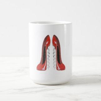 El estilete rojo del sacacorchos calza la taza