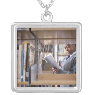 El estudiante en uniforme escolar mira un libro en collar plateado