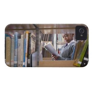 El estudiante en uniforme escolar mira un libro en iPhone 4 cobertura