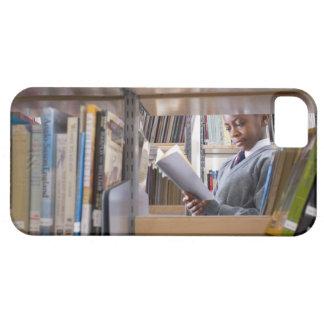 El estudiante en uniforme escolar mira un libro en iPhone 5 carcasa