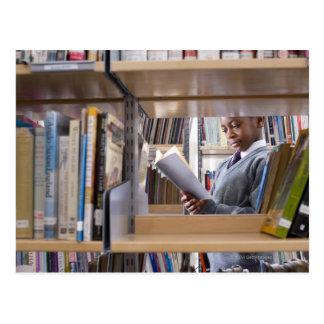 El estudiante en uniforme escolar mira un libro en tarjeta postal