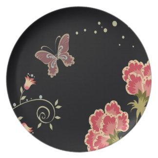 El extracto florece la mariposa negra de los color plato de comida