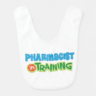 El farmacéutico en el entrenamiento embroma la baberos de bebé