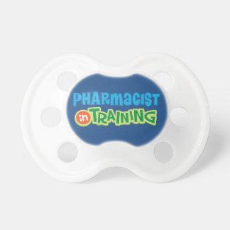 El farmacéutico en el entrenamiento embroma la chupetes de bebe