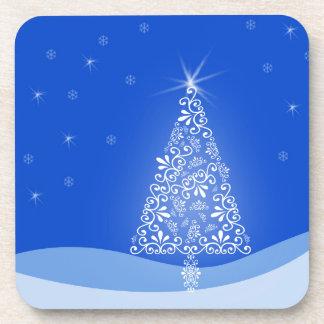 El feliz árbol de navidad blanco azul protagoniza posavasos de bebida