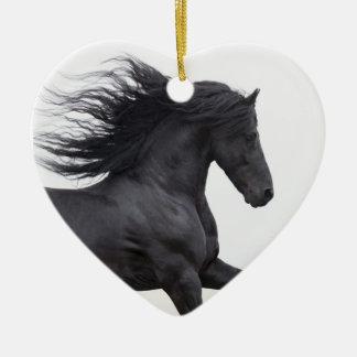 El frisio negro funciona con el ornamento del adorno navideño de cerámica en forma de corazón