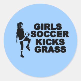 El fútbol de los chicas golpea la hierba con el pi etiqueta redonda