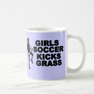 El fútbol de los chicas golpea la hierba con el pi tazas de café