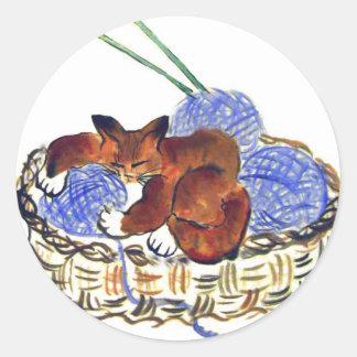 El gatito abraza una almohada del hilado pegatina redonda
