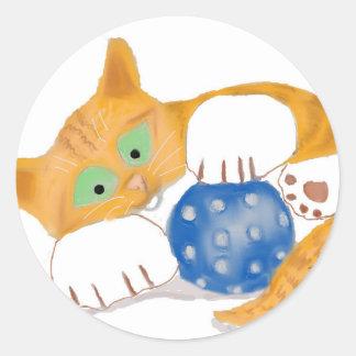 El gatito anaranjado del tigre juega con una bola pegatina redonda