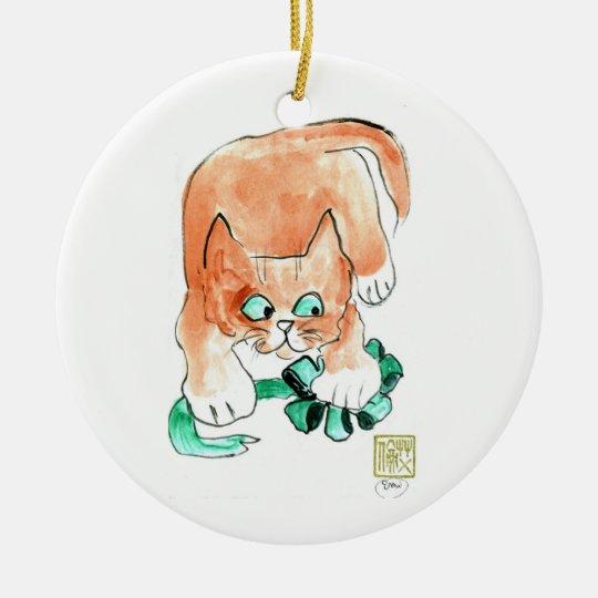 El gatito ataca un arco verde adorno navideño redondo de cerámica