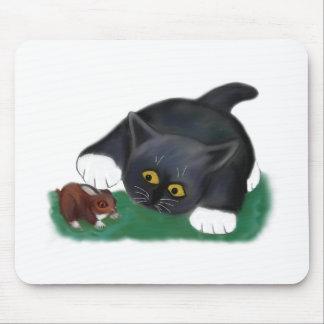 El gatito blanco y negro del smoking acaricia a su alfombrillas de ratones