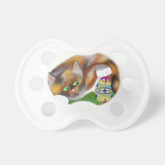 El gatito del calicó golpea ligeramente un huevo chupetes para bebes