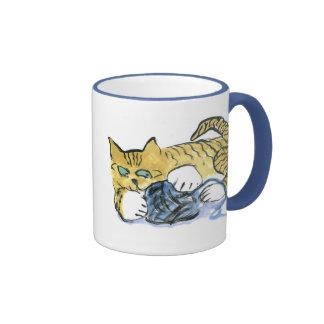 El gatito del tigre guarda sus ojos en el hilado taza de dos colores