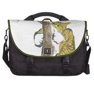 El gatito del tigre sube el árbol que persigue un  bolsas de portátil