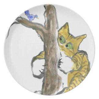 El gatito del tigre sube el árbol que persigue un  platos