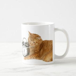 El gatito despierta tazas de café