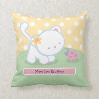 El gatito dulce embroma las almohadas de tiro